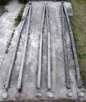 Auf Betonfläche arrangierte Betonpfähle und Natursteine