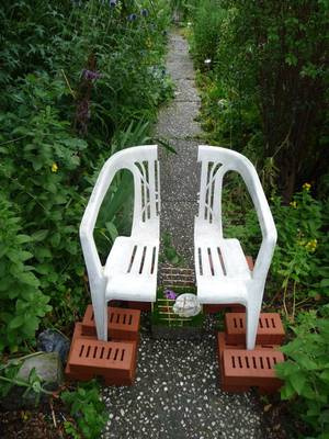Geteilter Plastikstuhl, Beine von Ziegeln umstellt, in der Mitte Rasen, Zäunchen, Kaffeetasse, Blume, Johannisbeeren