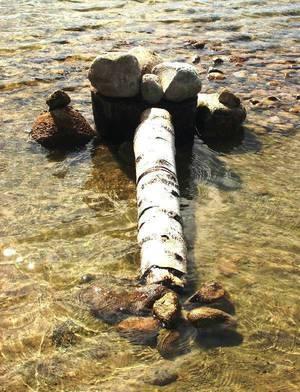 Landart: Baumstamm, Stein im See