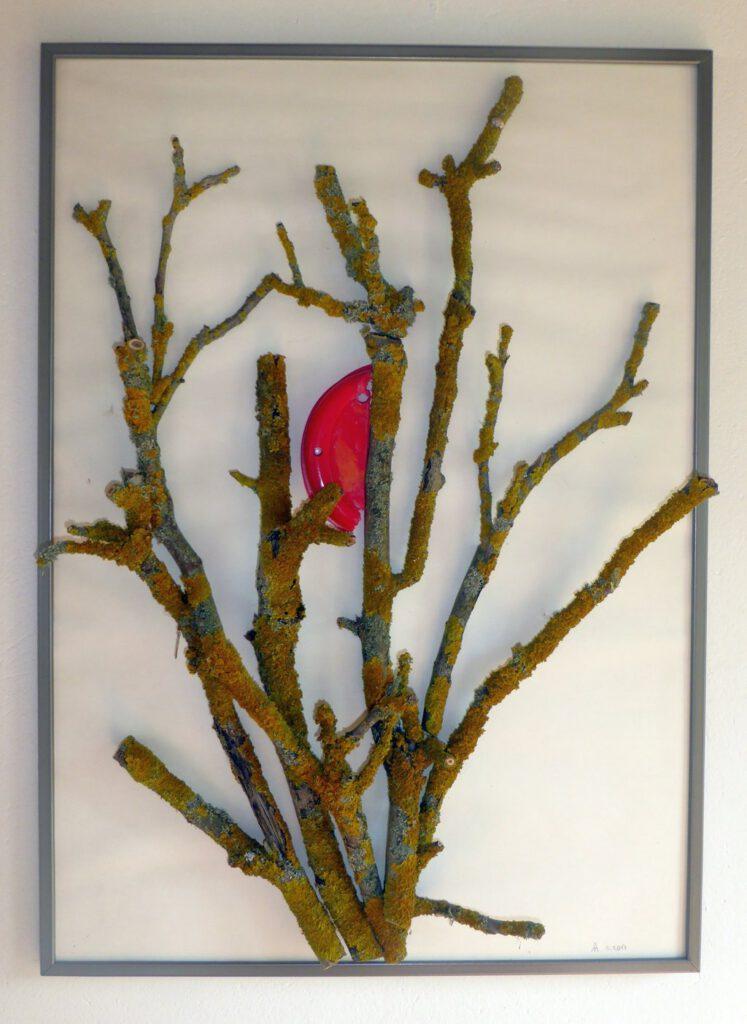 Toasterflechte. Collage, Storkow, 2017, Äste mit gelber Flechte, rotes Plastik aus einem Billigtoaster, 42 x 60 cm. Die Natur lebt mit uns.